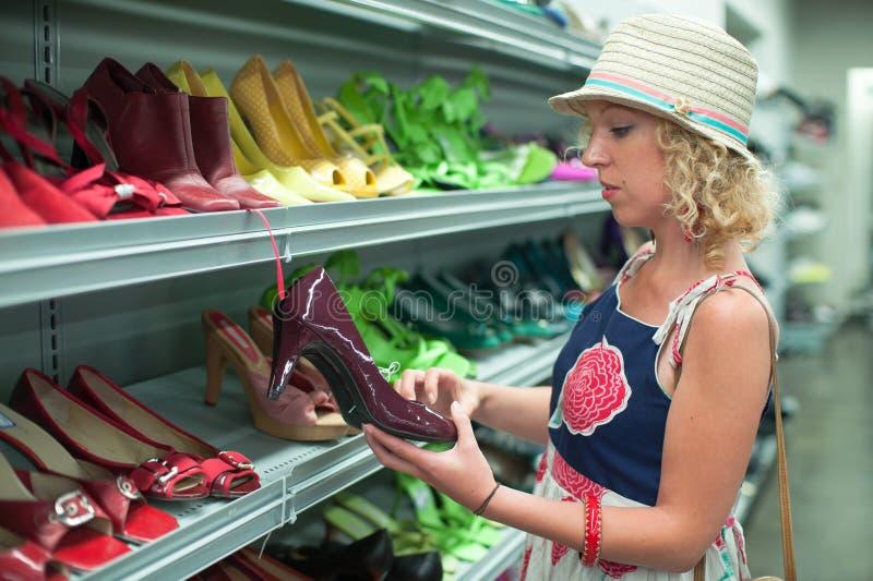Compra da sapata em uma loja de produtos usados fotografia de stock