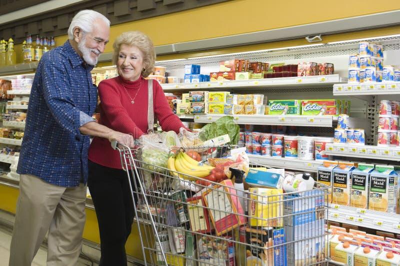 Compra de comida mayor de los pares en supermercado imagen de archivo libre de regalías