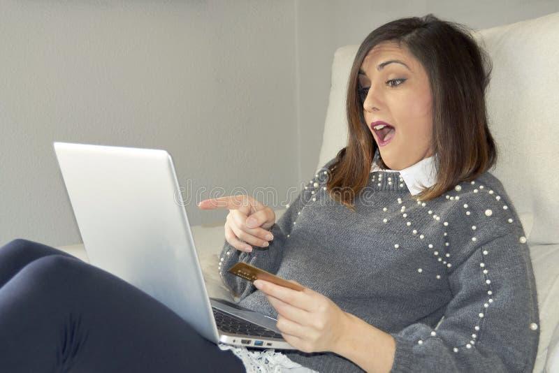 Compra de la mujer con un ordenador portátil en el sofá fotos de archivo