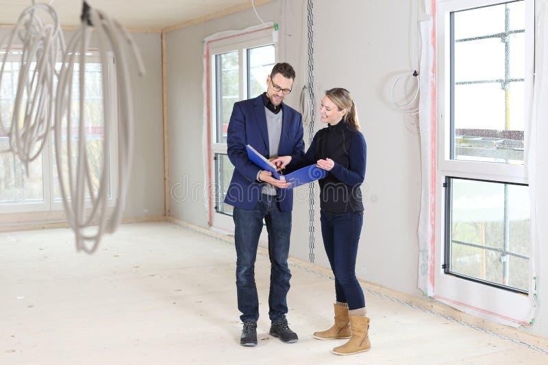 Compra de las propiedades inmobiliarias con el agente o arquitecto y mujer fotografía de archivo libre de regalías
