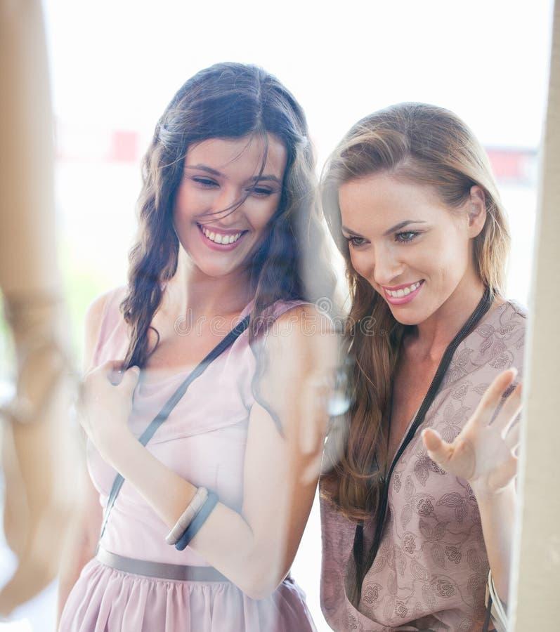 Compra de sorriso da janela de duas mulheres foto de stock royalty free