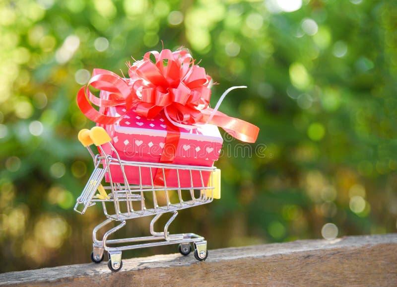 Compra do dia de Valentim e caixa atual da caixa de presente com curva vermelha da fita em férias de compra em linha do carrinho  foto de stock