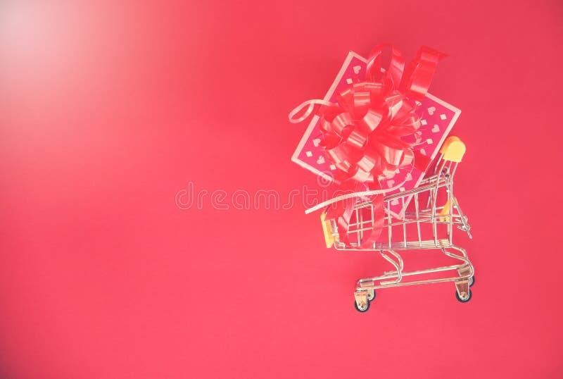 Compra do dia de Valentim e caixa de presente/caixa atual cor-de-rosa com curva vermelha da fita no carrinho de compras fotografia de stock