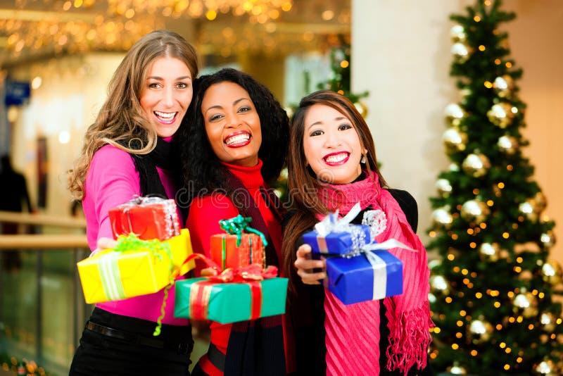 Compra do Natal dos amigos com presentes na alameda fotografia de stock royalty free