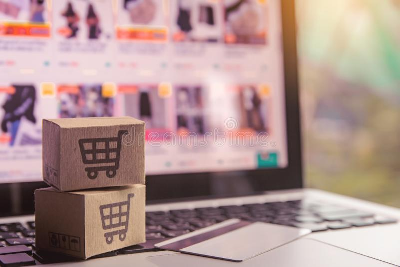 Compra em linha - caixas de papel ou pacote com um cartão do logotipo e de crédito do carrinho de compras em um teclado do portát foto de stock