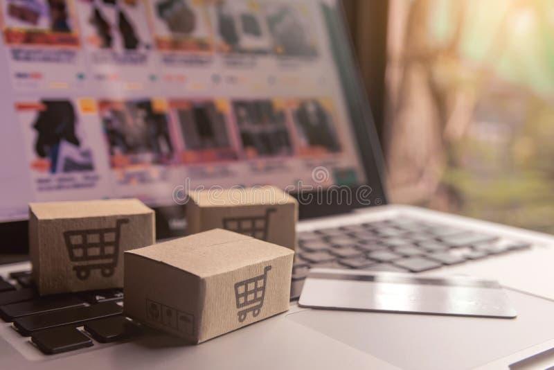 Compra em linha - caixas de papel ou pacote com um cartão do logotipo e de crédito do carrinho de compras em um teclado do portát foto de stock royalty free