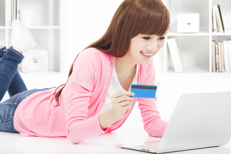 Compra em linha da jovem mulher em casa com cartão de crédito foto de stock royalty free