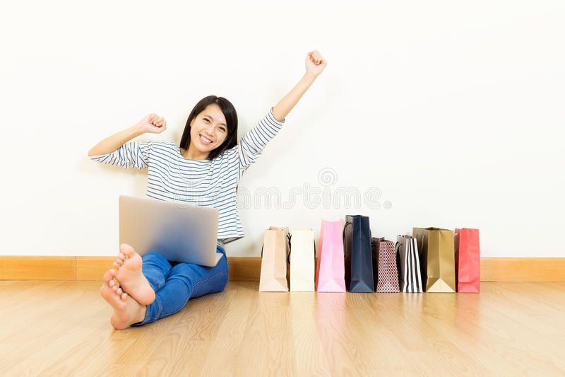Compra em linha da mulher asiática em casa com saco de papel sortido imagens de stock royalty free