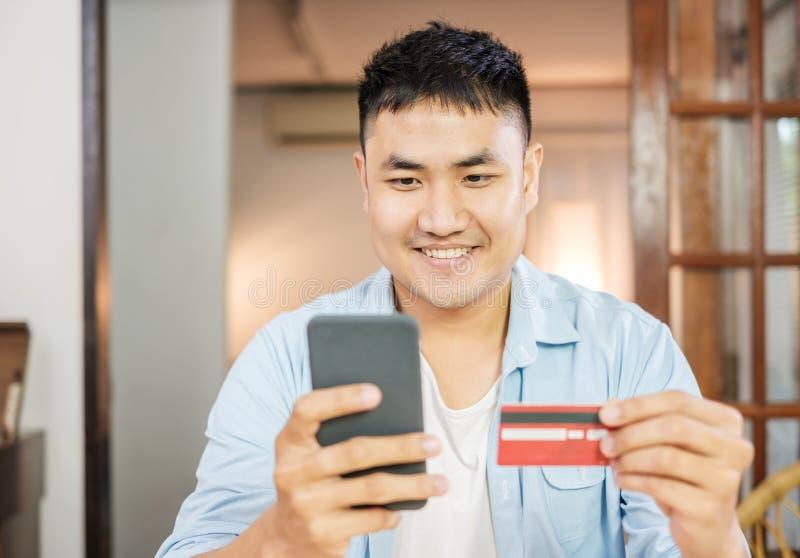 Compra em linha do homem asiático com cartão e telefone celular de crédito em casa estilo de vida digital com tecnologia imagens de stock royalty free