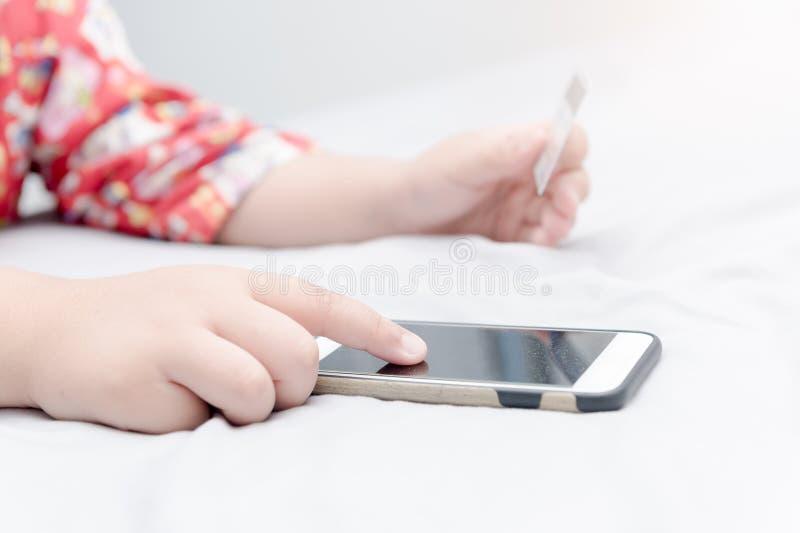 Compra em linha Mãos que guardam o cartão de crédito e que usam o smartphone imagem de stock