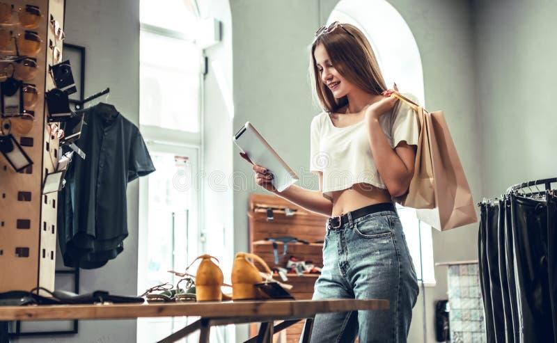 Compra em linha ou não? Mulher bonita com a tabuleta digital na loja A morena elegante na roupa à moda escolhe sapatas imagens de stock royalty free