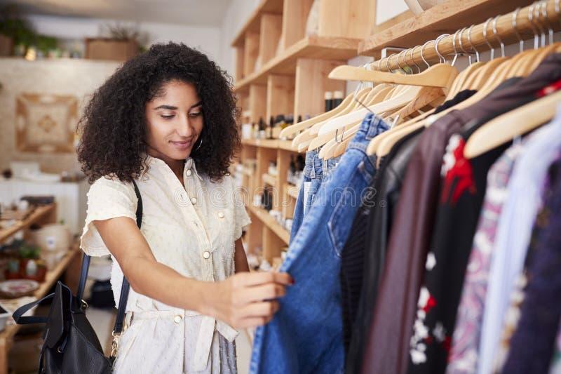 Compra fêmea do cliente na loja de roupa independente que olha cremalheiras fotografia de stock