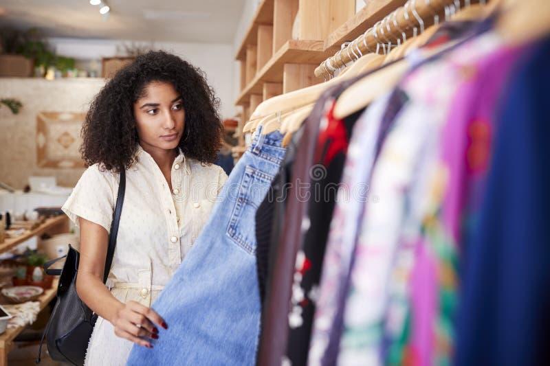 Compra f?mea do cliente na loja de roupa independente que olha cremalheiras foto de stock royalty free