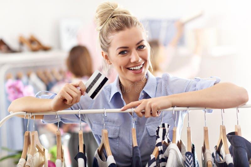 Compra feliz da mulher para a roupa com cartão de crédito fotografia de stock royalty free