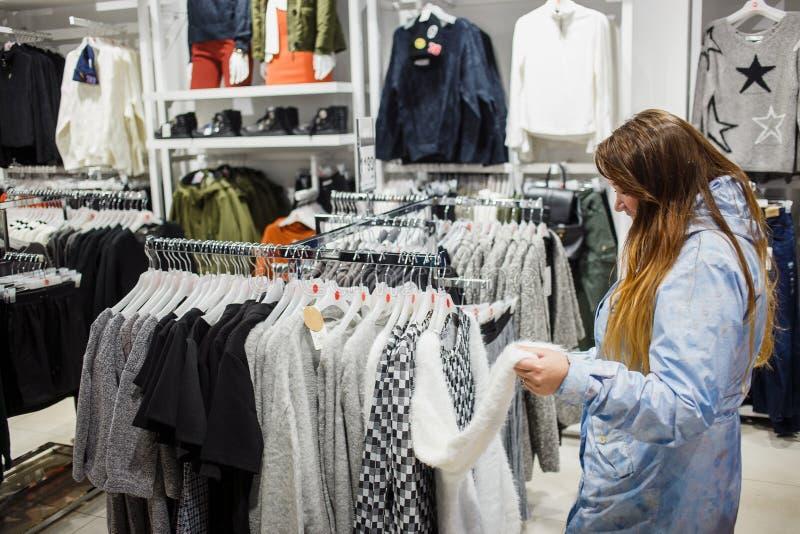 Compra, forma, venda, estilo e conceito dos povos - jovem mulher no casaco azul que escolhe o revestimento leve na loja de roupa imagem de stock royalty free