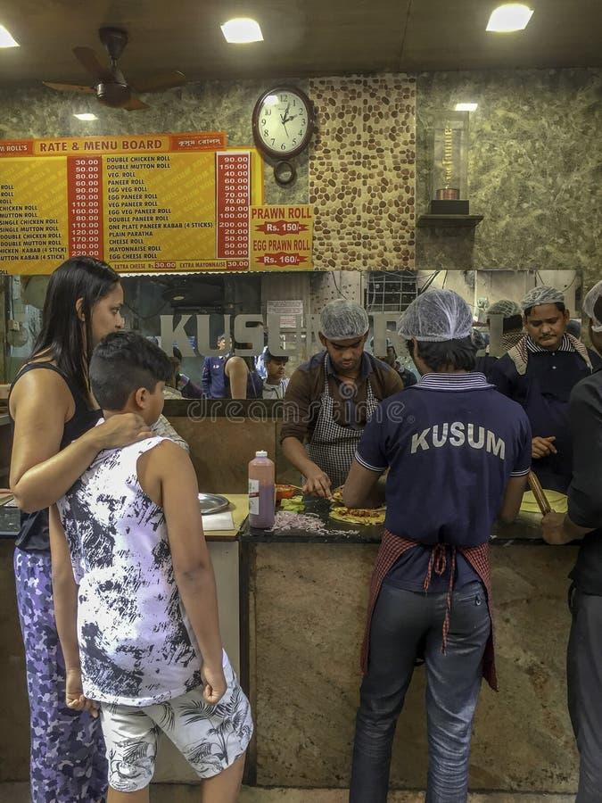 Compra Kusum' da mulher e do menino; rolos do kathi de s imagem de stock royalty free