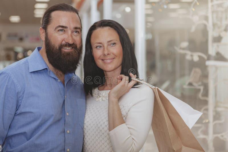 Compra madura feliz dos pares na alameda fotografia de stock royalty free