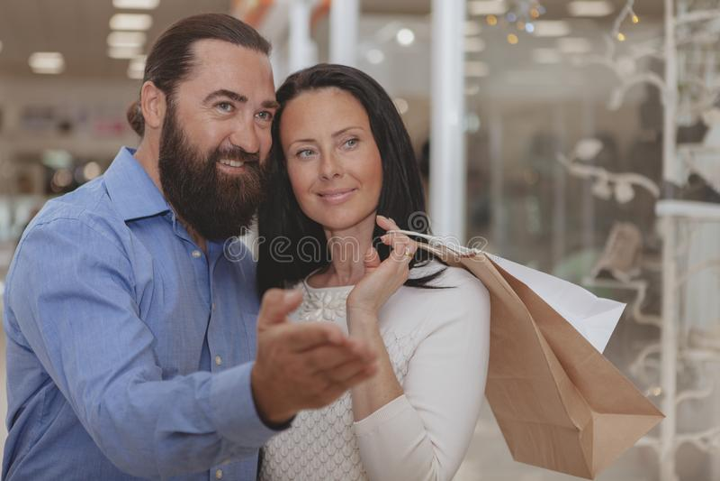 Compra madura feliz dos pares na alameda imagem de stock