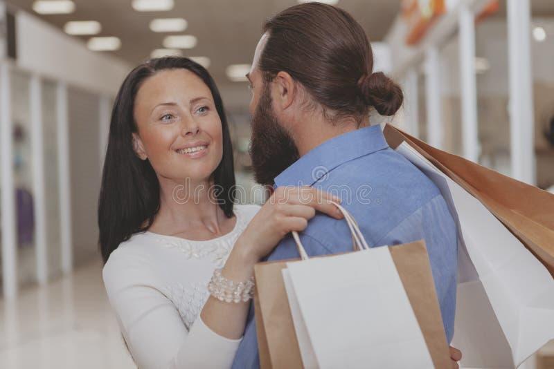 Compra madura feliz dos pares na alameda imagens de stock royalty free