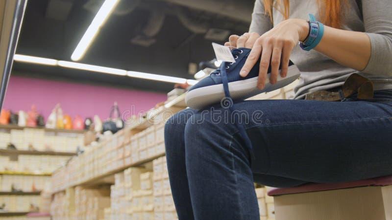Compra mulheres - a menina escolhe sapatas na alameda fotografia de stock