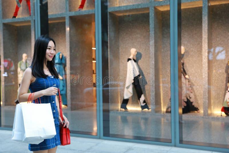 Compra na moda nova oriental oriental chinesa feliz da menina da mulher de Ásia na alameda com fundo de compra da janela dos saco imagens de stock