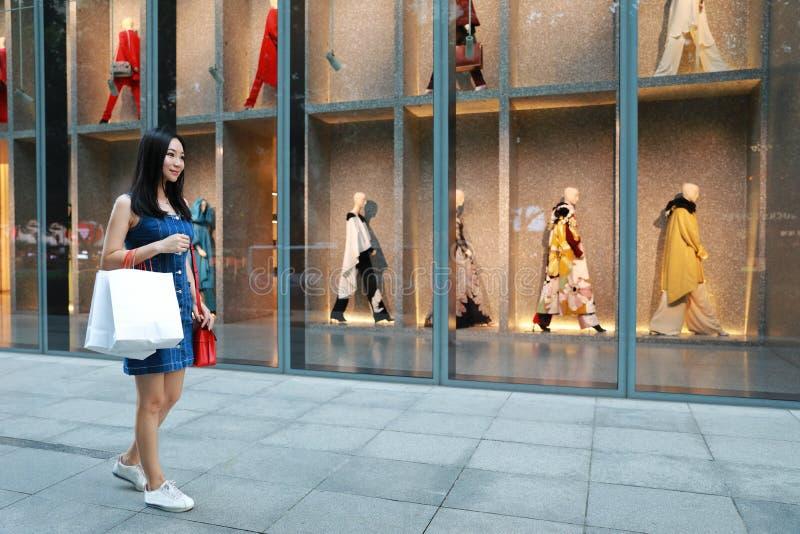 Compra na moda nova oriental oriental chinesa feliz da menina da mulher de Ásia na alameda com fundo de compra da janela dos saco imagem de stock