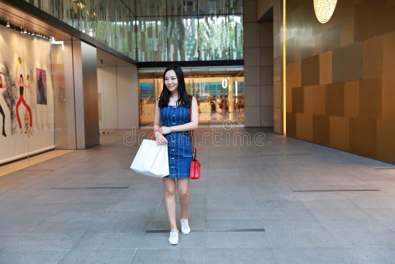 Compra na moda nova oriental oriental chinesa feliz da menina da mulher de Ásia na alameda com fundo de compra da janela dos saco foto de stock royalty free