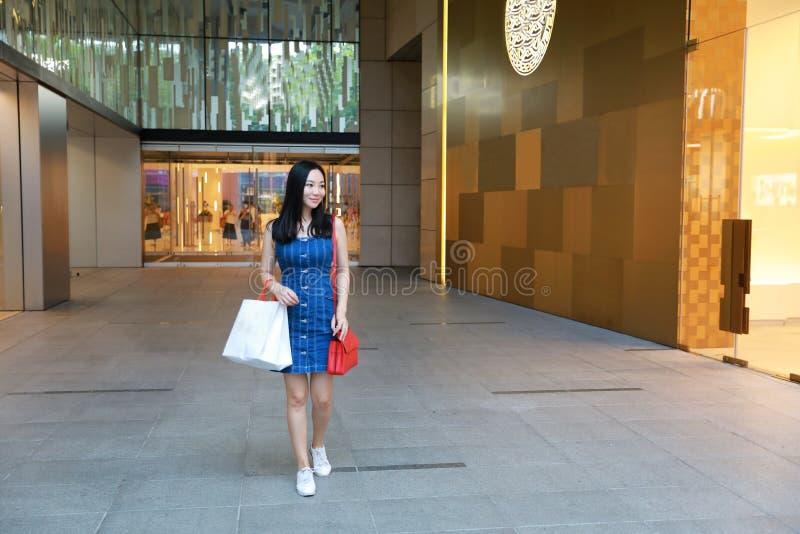 Compra na moda nova oriental oriental chinesa feliz da menina da mulher de Ásia na alameda com fundo de compra da janela dos saco imagens de stock royalty free