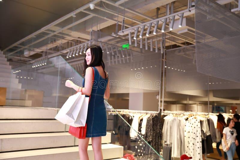 Compra na moda nova oriental oriental chinesa feliz da menina da mulher de Ásia na alameda com fundo de compra da janela dos saco fotos de stock