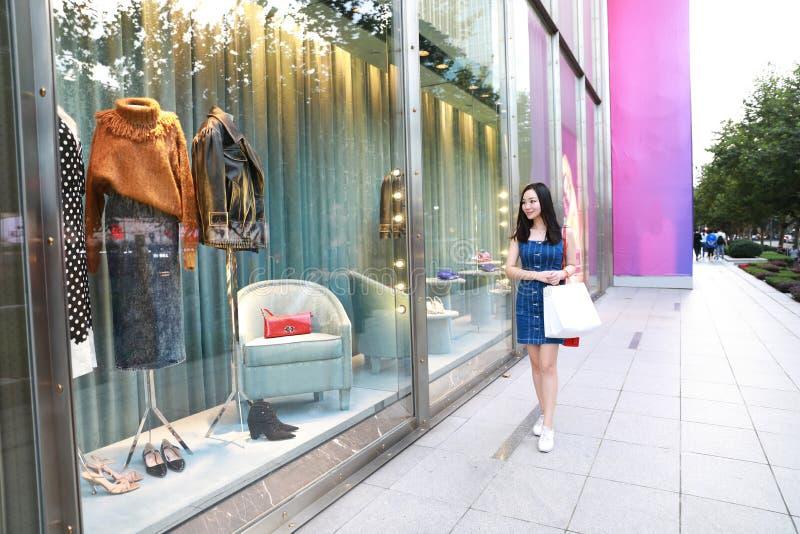 Compra na moda nova oriental oriental chinesa feliz da menina da mulher de Ásia na alameda com fundo de compra da janela dos saco foto de stock