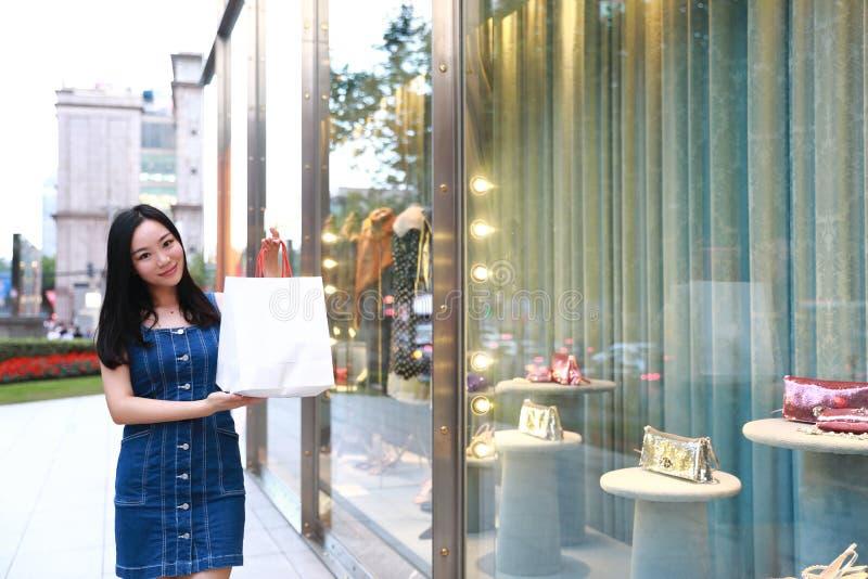 A compra na moda nova oriental oriental chinesa feliz da menina da mulher de Ásia na alameda com sacos olha a janela da compra na fotografia de stock