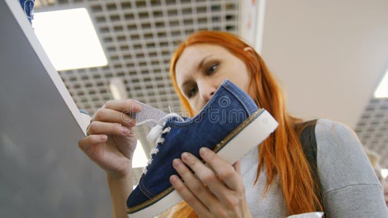 Compra no centro do comércio da alameda - a mulher escolhe as sapatilhas na loja de sapatas foto de stock