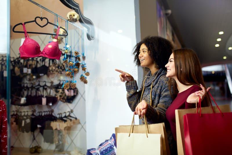 A compra nova multi-étnico feliz da mulher da raça dois misturada para a roupa interior perto da janela da loja do boutique da ro fotos de stock royalty free
