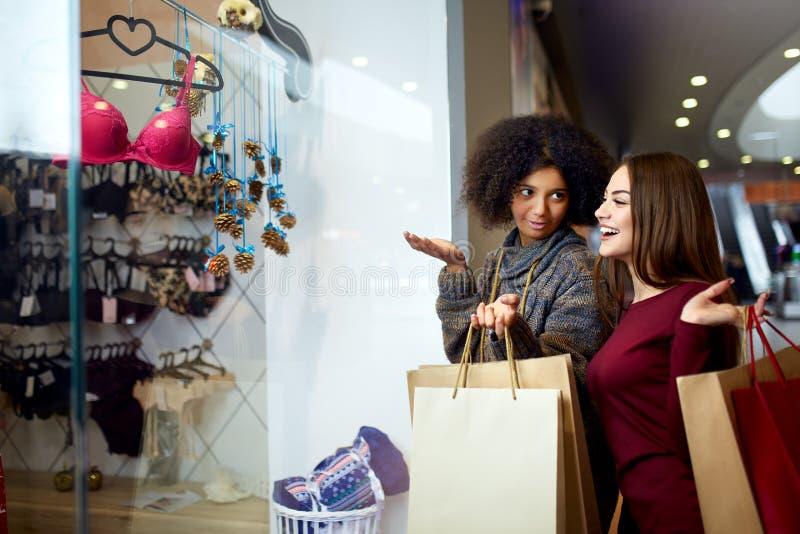 A compra nova multi-étnico feliz da mulher da raça dois misturada para a roupa interior perto da janela da loja do boutique da ro imagem de stock royalty free