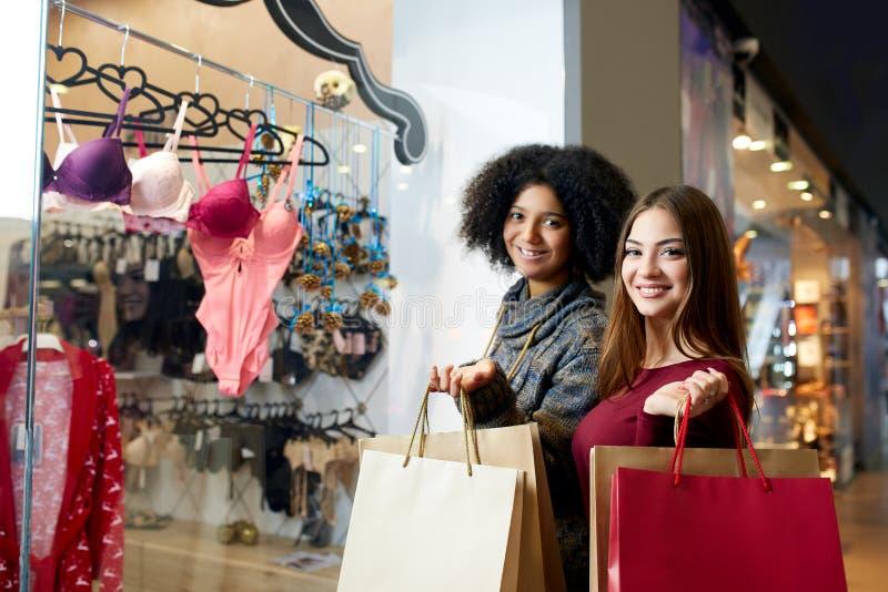 A compra nova multi-étnico feliz da mulher da raça dois misturada para a roupa interior perto da janela da loja do boutique da ro foto de stock