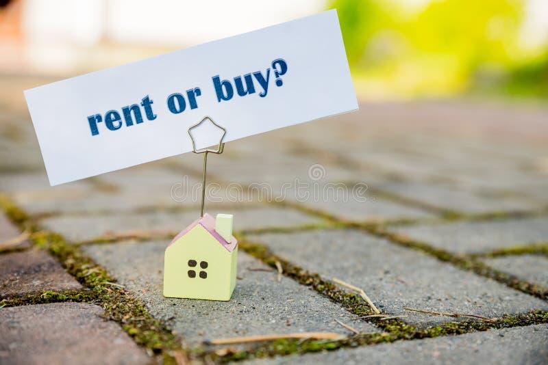 Compra ou aluguel da mensagem de texto no suporte da foto da casa pequena Conceito do negócio chouce duro empréstimos, débito de  fotos de stock royalty free