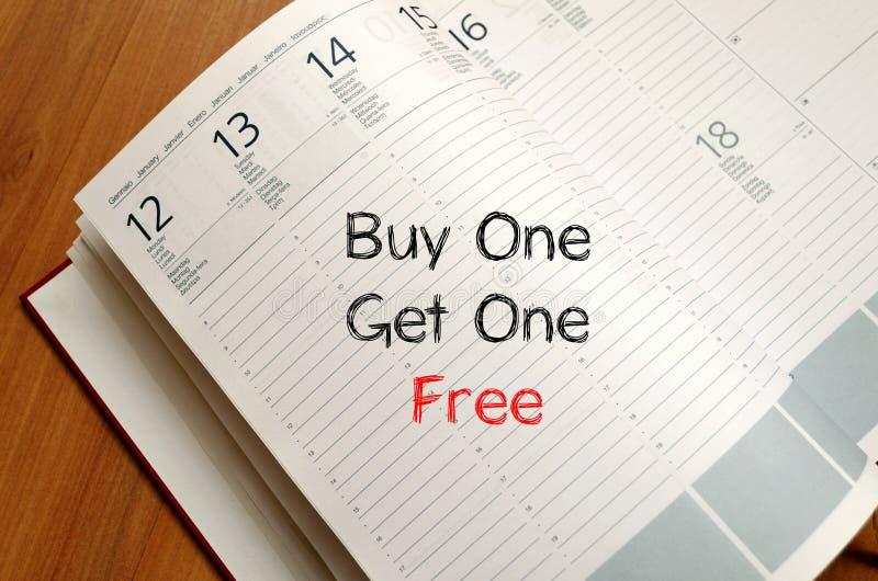 A compra uma obtém um livre escreve no caderno fotos de stock royalty free