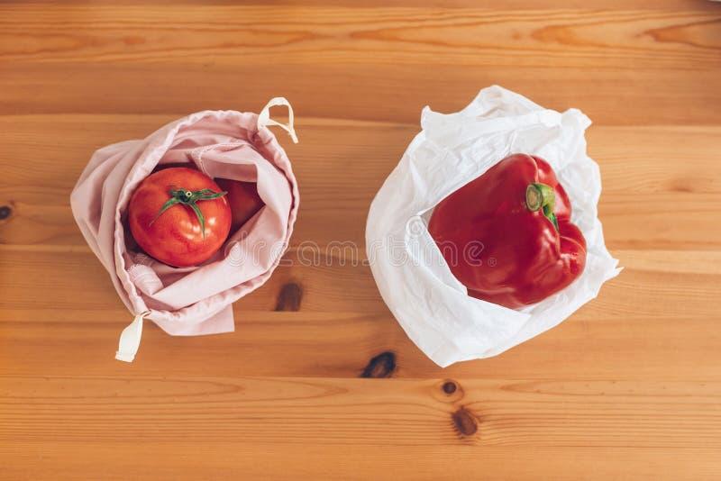 Compra zero do desperdício, configuração lisa Mantimentos frescos em sacos reusáveis do eco e vegetais no saco de polietileno plá foto de stock