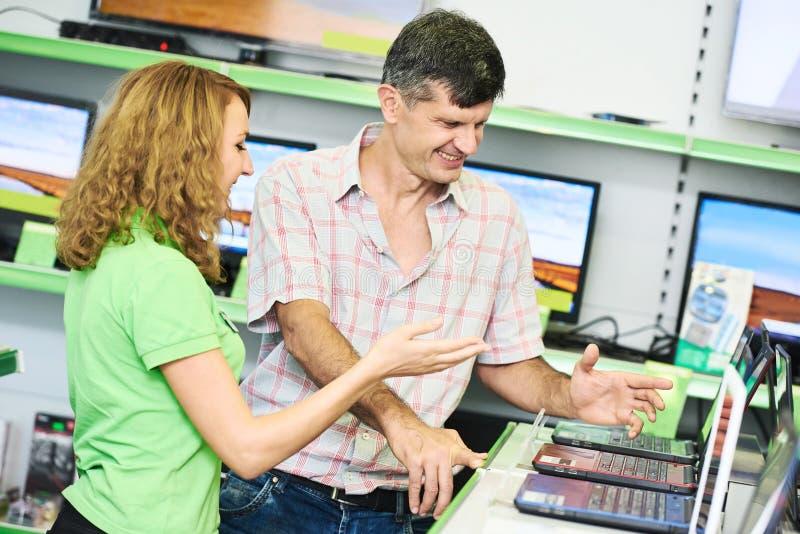 Comprador auxiliar de la ayuda de la mujer del vendedor que elige el ordenador portátil fotografía de archivo