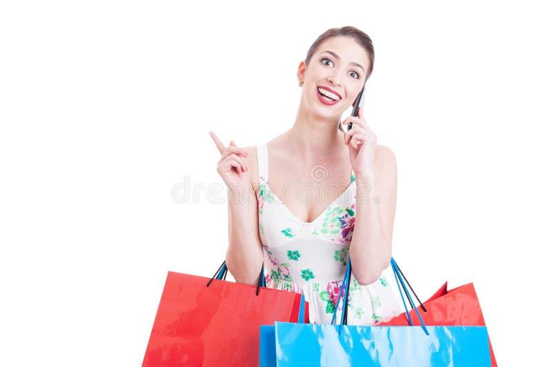 Comprador bonito de la señora que tiene una llamada y que siente sorprendido fotografía de archivo