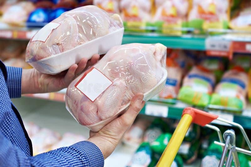 Comprador da carne da galinha na loja foto de stock