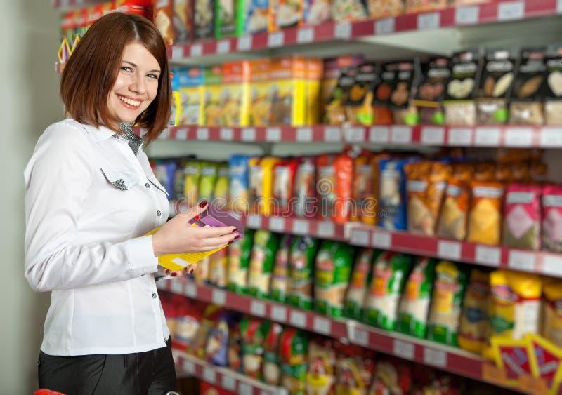 Comprador de mulher bonito na loja de mantimento imagem de stock