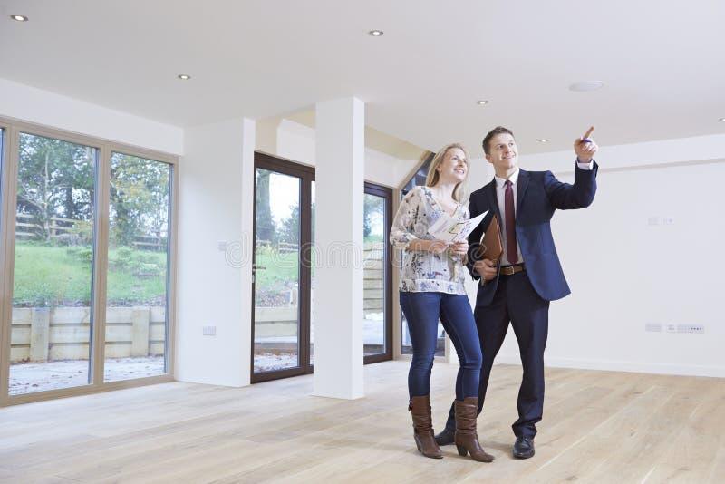 Comprador de Showing Prospective Female del agente de la propiedad inmobiliaria alrededor de la propiedad fotografía de archivo