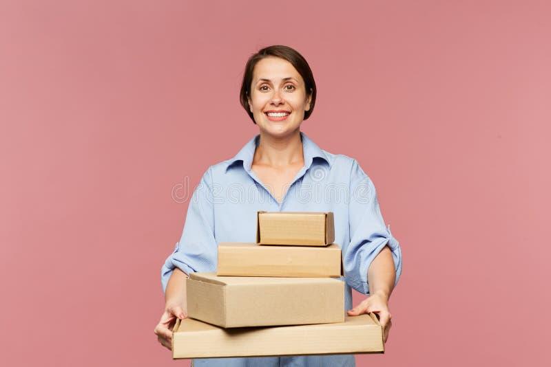 Comprador en línea femenino alegre joven con la pila de órdenes llenas fotografía de archivo