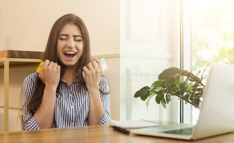 Comprador eufórico que compra en línea con el ordenador portátil y la tarjeta de crédito imagen de archivo libre de regalías