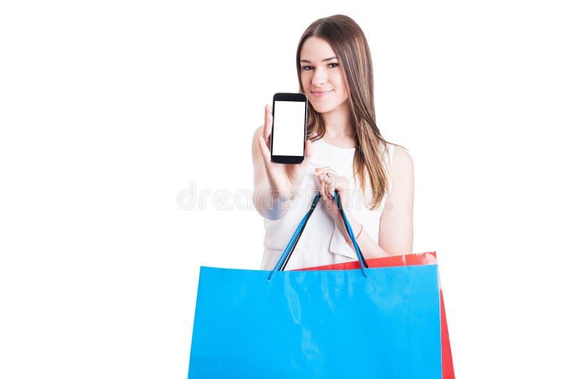 Comprador feliz con los panieres que muestran un scre en blanco del smartphone imagenes de archivo