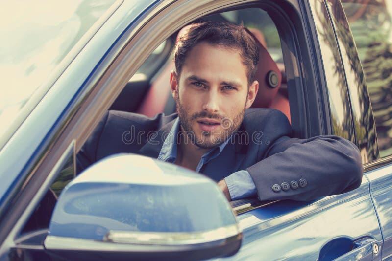 Comprador feliz del hombre que se sienta en su nuevo coche listo para el viaje imagen de archivo
