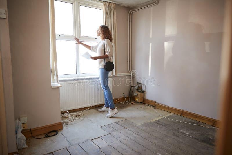 Comprador femenino de la primera vez que mira encuesta sobre la casa en sitio de ser renovado imagenes de archivo
