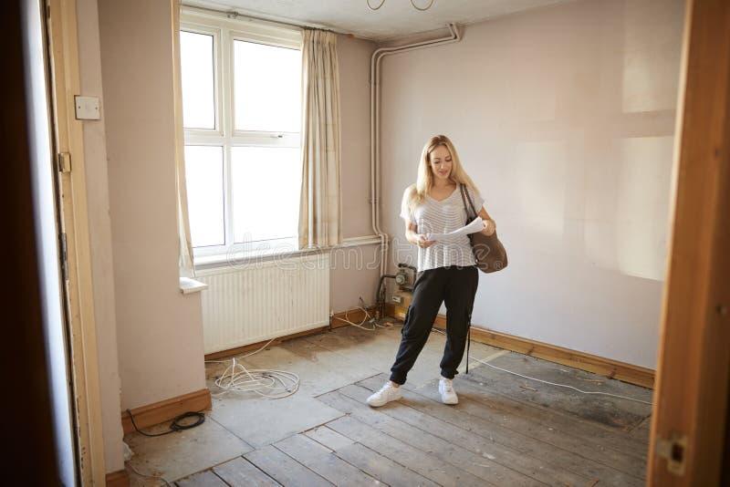 Comprador femenino de la primera vez que mira encuesta sobre la casa en sitio de ser renovado imágenes de archivo libres de regalías