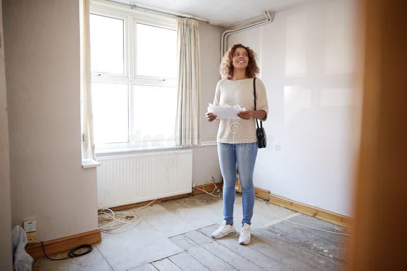 Comprador femenino de la primera vez que mira encuesta sobre la casa en sitio de ser renovado foto de archivo